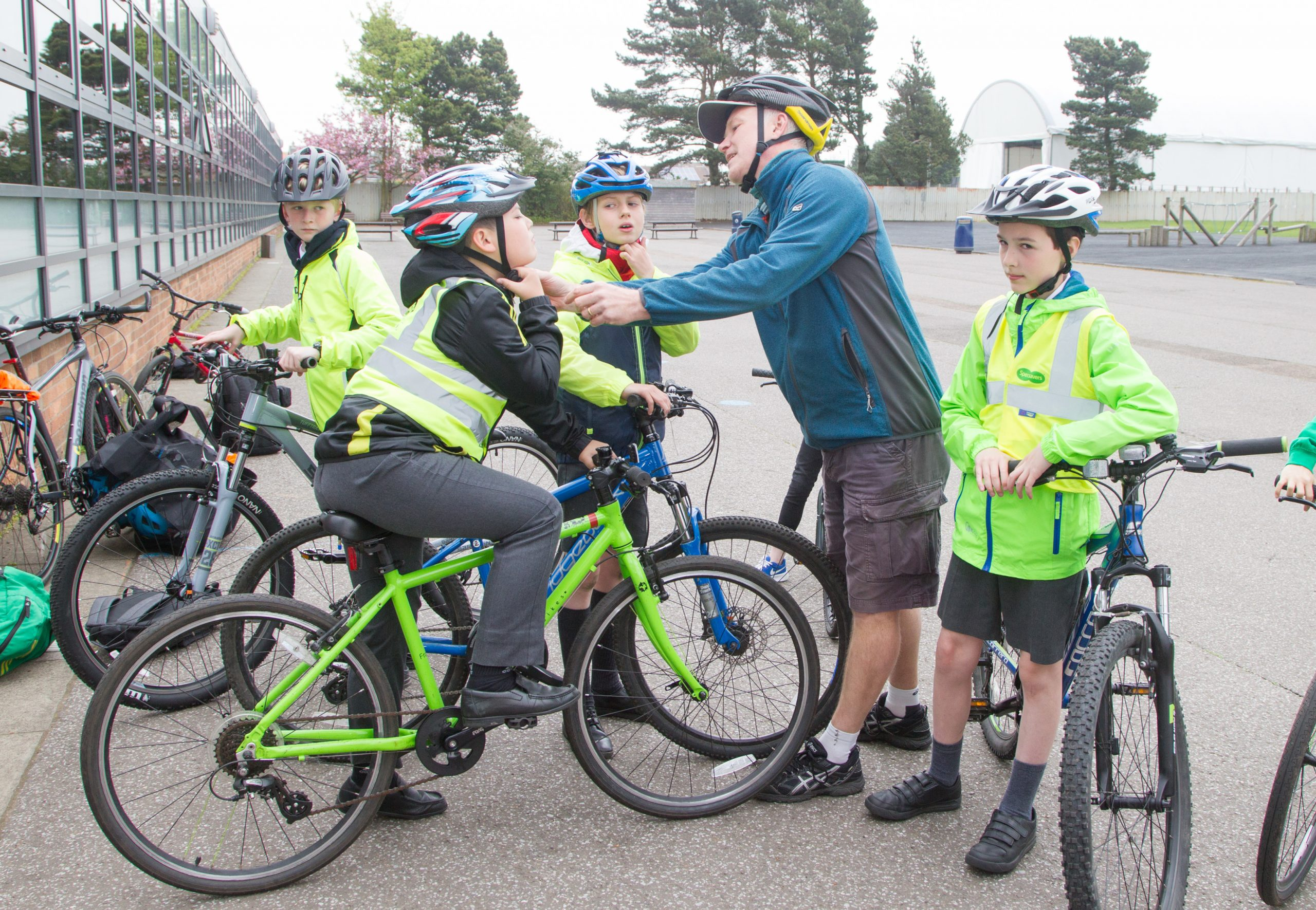 Helmet fitting pupils helped by an I Bike volunteer